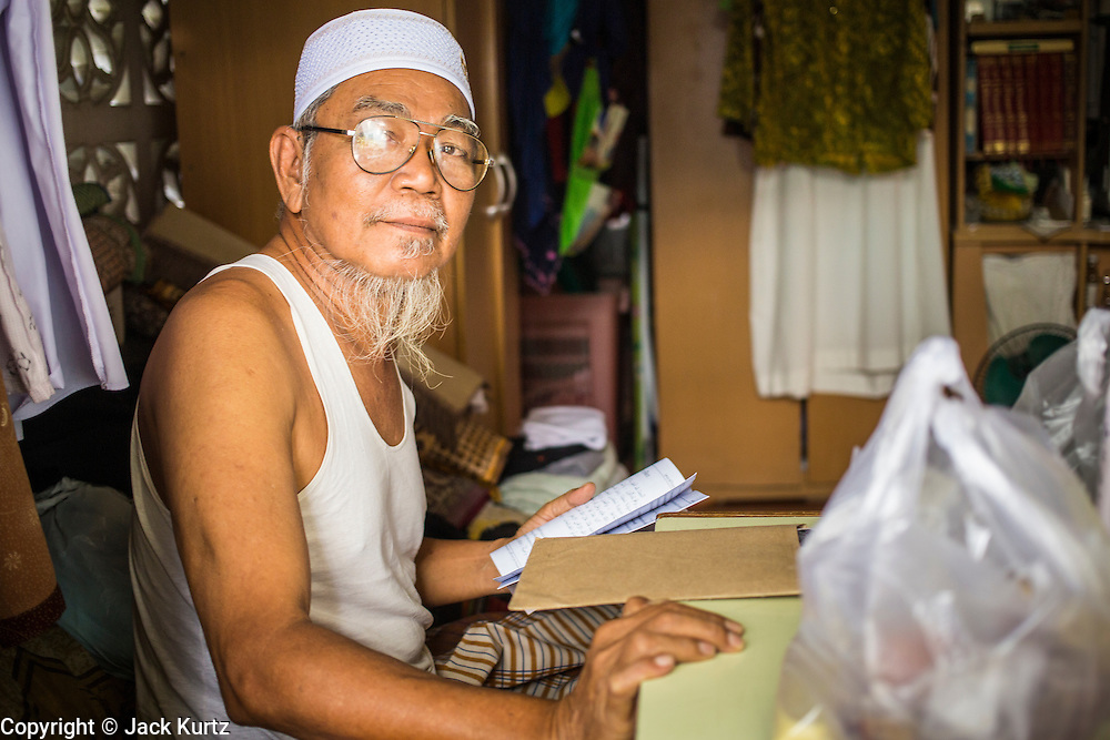"11 JANUARY 2013 - BANGKOK, THAILAND:    A Muslim man in his home in the Ban Krua neighborhood in Bangkok. The Ban Krua neighborhood of Bangkok is the oldest Muslim community in Bangkok. Ban Krua was originally settled by Cham Muslims from Cambodia and Vietnam who fought on the side of the Thai King Rama I. They were given a royal grant of land east of what was then the Thai capitol at the end of the 18th century in return for their military service. The Cham Muslims were originally weavers and what is known as ""Thai Silk"" was developed by the people in Ban Krua. Several families in the neighborhood still weave in their homes.       PHOTO BY JACK KURTZ"