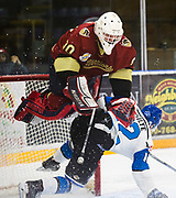 Goaltender Brock Baier goes flying as Penticton's David Silye slides into the net during third period BCHL action at Royal LePage Place in West Kelowna, B.C. The West Kelowna Warriors beat the Penticton Vees 3-2. (Marissa Tiel/ Kelowna Capital News)