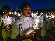 """22 FEBRUARY 2016 - KHLONG LUANG, PATHUM THANI, THAILAND: People participate in the candle light procession around the chedi during the Makha Bucha Day service at Wat Phra Dhammakaya.  Makha Bucha Day is a public holiday in Cambodia, Laos, Myanmar and Thailand. Many people go to the temple to perform merit-making activities on Makha Bucha Day, which marks four important events in Buddhism: 1,250 disciples came to see the Buddha without being summoned, all of them were Arhantas, Enlightened Ones, and all were ordained by the Buddha himself. The Buddha gave those Arhantas the principles of Buddhism, called """"The ovadhapatimokha"""". Those principles are:  1) To cease from all evil, 2) To do what is good, 3) To cleanse one's mind. The Buddha delivered an important sermon on that day which laid down the principles of the Buddhist teachings. In Thailand, this teaching has been dubbed the """"Heart of Buddhism."""" Wat Phra Dhammakaya is the center of the Dhammakaya Movement, a Buddhist sect founded in the 1970s and led by Phra Dhammachayo.      PHOTO BY JACK KURTZ"""