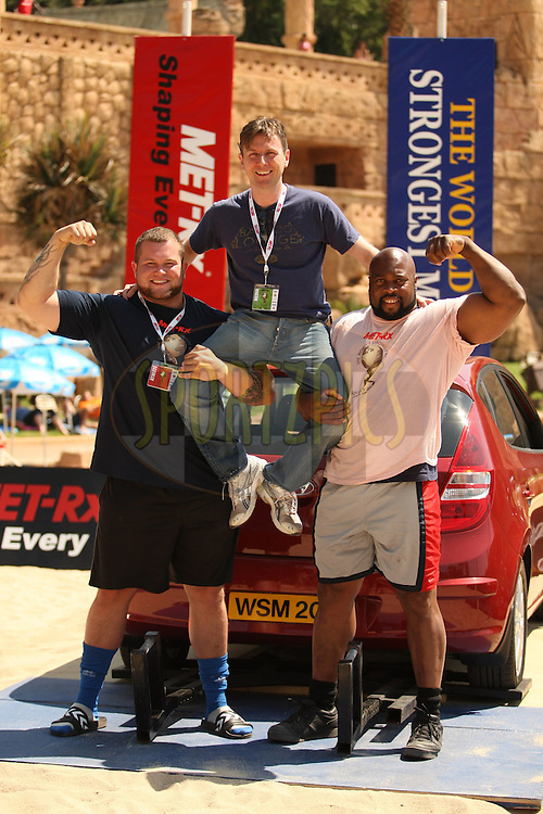 Journalist Alistair Ross (The Sun, UK) is held up by Stefan Solvi Peturssen (Iceland) and Mark Felix (UK) at the World's Strongest Man competition held in Sun City, South Africa.
