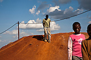 Kipushi, DRC. March 2009. In a town that relied heavily on mining activity, it was devastating when state-owned Gecamine ceased operating in 1993 as a result of financial problems after 68 years of operations. Gathering storm clouds signal the end of the day on these discarded mine dumps, where entire families have spent the day breaking up rocks by hand. The rain will bring a welcome break in the intense heat of this Congolese border town.