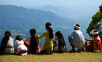 A group of colorfully dressed children are looking out over the beautiful landscape at Puri Agung, Bali, Indonesia