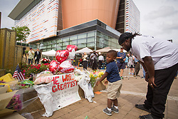 Cortez Hampton Jr., 3, left, looks at a sign left for Legendary heavyweight boxing champion Muhammad Ali, a Louisville, Ky., native with his father Cortez Hampton Sr. Ali died Friday, June 3, 2016. <br /> <br /> Murals and tributes could be seen across his hometown as people mourned the charismatic sports figure.