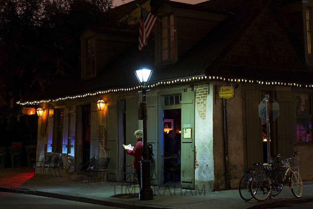 Tourist under lamp post by Lafitte Jazz bar in famous Bourbon Street in French Quarter of New Orleans, USA