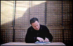 The Prime Minister David Cameron writing a Christmas Bluey Message at Camp Bastion on a visit to Afghanistan. Monday, 16th December 2013. Picture by Andrew Parsons / i-Images