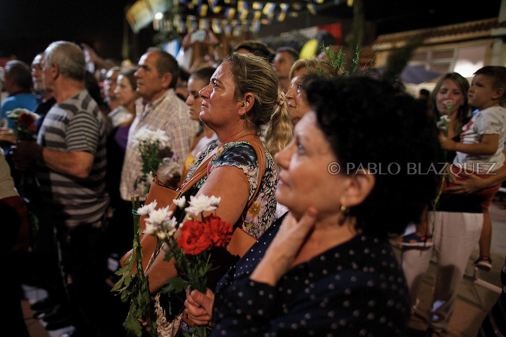 15/08/2016. Worshippers watch as fishermen carry the image of the Virgin of Palm back to the sea during the yearly Virgin of Palm maritime pilgrimage at El Rinconcillo beach on August 15, 2016 in Algeciras, Spain. The Our Lady of Palm maritime pilgrimage in Algeciras dates back to 1975 and takes place annually when fishermen rescue the submerged virgin from the deep sea. Worshippers amid thousands of visitors await its arrival at the Rinconcillo beach. The devotion for the Virgin of Palm comes from the seventeenth century when a ship coming from Italy docked at Algeciras port to wait out bad weather. According to legend, once the crew of the ship removed a box with an image of the Virgin from its cargo the weather turned and the sea's tides were calmed. (© Pablo Blazquez)