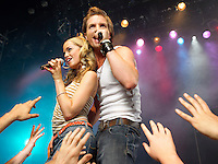 Young man and woman singing on stage in concert in front of adoring fans low angle view