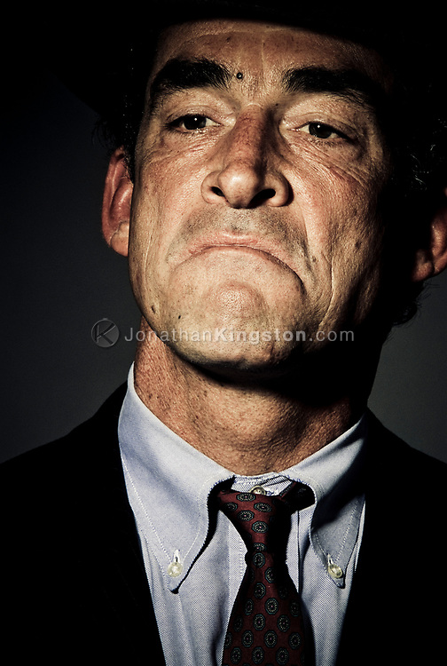 Low angle, close up, front view of a mature man in a business suit with a smug expression on his face.  Studio shot against a dark background. (releasecode: jk_mr1025) (Model Released)