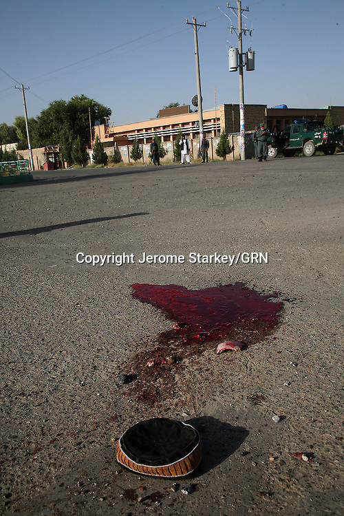 A cap of a young boy killed by a Taliban rocket lies next to a pool of blood, outside a polling station in the Helmand capital Lashkar Gah.