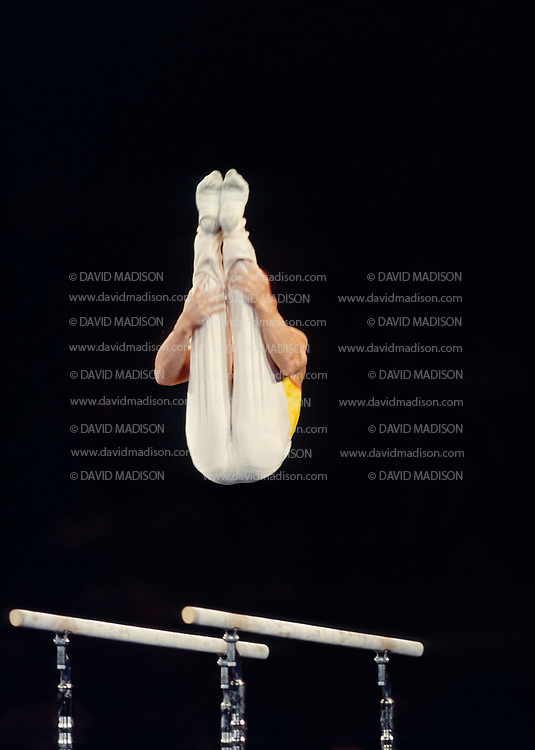 UNIONDALE, NY - JULY 1998:  Xu Huang of China competes on the parallel bars during the Men's Gymnastics competition of the Goodwill Games which took place from July 19 - August 2, 1998 in New York, New York.  The gymnastics venue was the Nassau Veterans Memorial Coliseum in Uniondale, New York.  (Photo by David Madison/Getty Images)