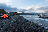 The migrants have moved on, but on a beach in Molyvos, on the north coast of the Greek island of Lesbos, the remains of their journey across the sea from Turkey are visible. On the left is a mound containing life jackets as well as the rubber remains of inflatable boats. On the right is a beached ship that earlier in the month had carried one group of migrants to the island.