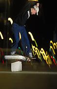Skateboarder, Ben Alnut, doing a rail-slide on a concrete bench, UK, 2000's