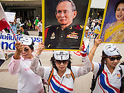 "14 JULY 2013 - BANGKOK, THAILAND:  Royalist supporters of the Thai monarchy hold up signs of Bhumibol Adulyadej, the King of Thailand, and his wife Queen Sirikit during an anti-government protest in Bangkok Sunday. About 150 members of the so called ""White Mask"" movement marched through the central shopping district of Bangkok Sunday to call for the resignation of Yingluck Shinawatra, the Prime Minister of Thailand. The White Mask protesters are strong supporters of the Thai monarchy. They claim that Yingluck is acting as a puppet for her brother, former Prime Minister Thaksin Shinawatra, who was deposed by a military coup in 2006 and now lives in exile in Dubai.       PHOTO BY JACK KURTZ"