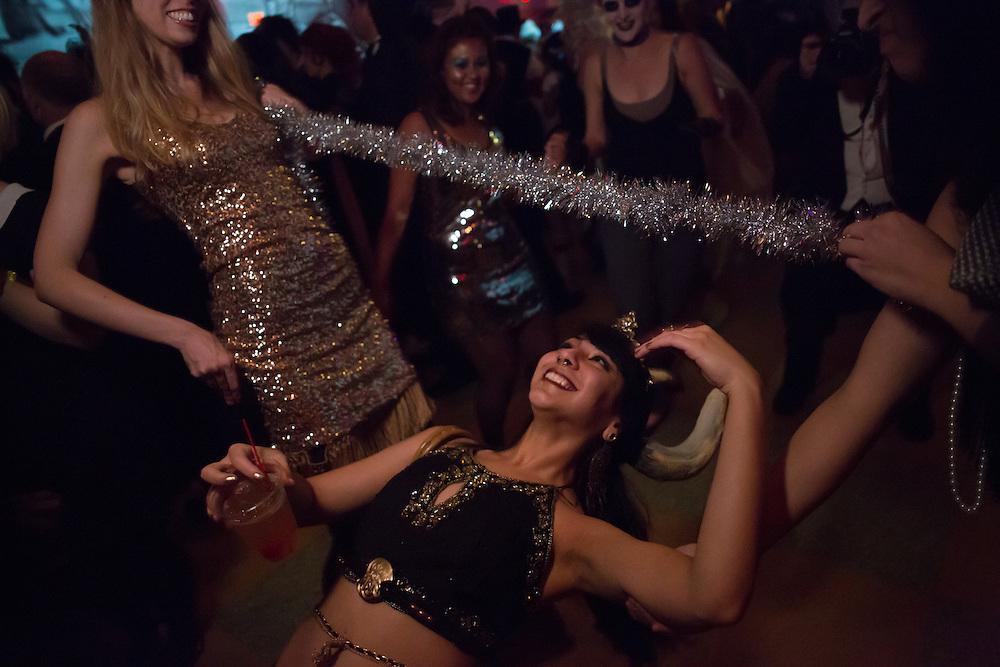 A woman with horns dances under a limbo bar.