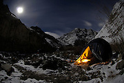 Leh - Tuesday, Dec 05 2006: Surrounded by snow, mountains and rocks, a candle lights the entrance of a two man tent at night in the Rumbak Valley in Hemis National Park. This was the first base location for Peter Horrell's expedition to search for and photograph snow leopards in their natural environment. (Photo by Peter Horrell / http://www.peterhorrell.com)