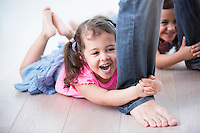 Playful girls holding father's legs on hardwood floor