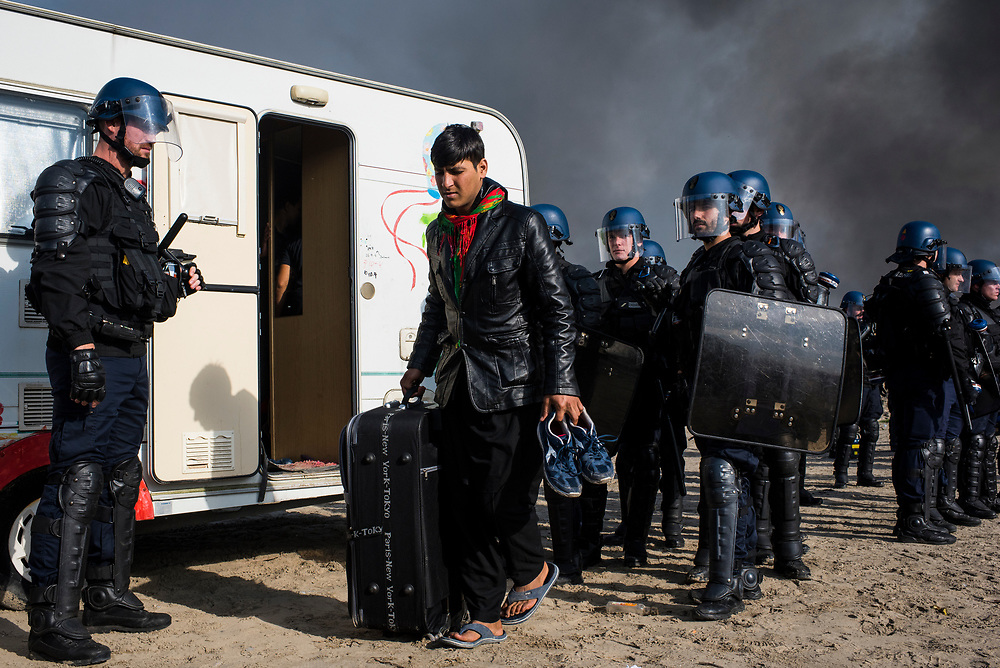Police order a refugee out of the trailer he was living in on October 26, 2016 at The Jungle refugee camp in Calais, France. On the third day of the operation to evict refugees and dismantle the camp, fires broke out in late morning and continued throughout the day, destroying large swaths of dwellings and businesses.