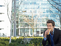 Mid adult businessman sitting in front of office building eating sandwich