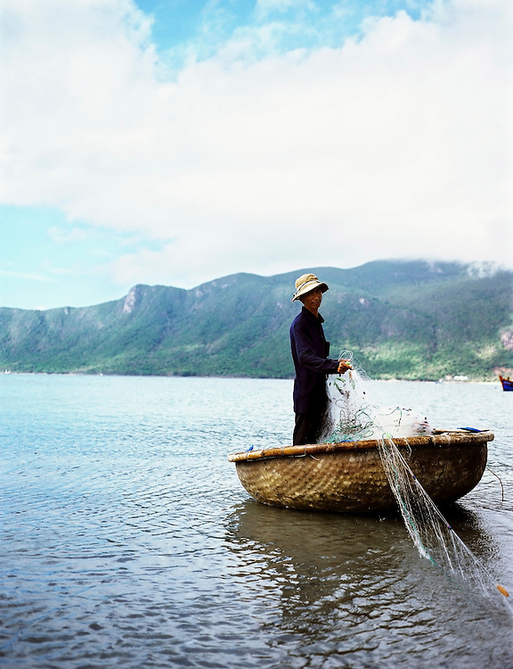 Fisherman pulling up nets into his coracle in Con Son harbor.