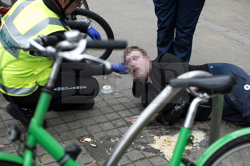 © Licensed to London News Pictures . 06/04/2017 . Manchester , UK . A paramedic tends to a man , believed to have consumed spice , as he lies on the pavement and vomits , on Piccadilly Gardens . An epidemic of abuse of the drug spice by some of Manchester's homeless population , in plain sight , is causing users to experience psychosis and a zombie-like state and is daily being witnessed in the Piccadilly Gardens area of Manchester , drawing large resource from paramedic services in the city centre . Photo credit : Joel Goodman/LNP
