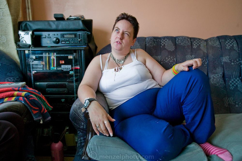 """Jill McTighe, a mother and school aide, sits on a couch at her home in Willesden, London, United Kingdom. (Jill McTighe is featured in the book What I Eat: Around the World in 80 Diets.)  The caloric value of her day's worth of food on a """"bingeing"""" day in the month of September was 12300 kcals. The calorie total is not a daily caloric average.  Jill is 31 years old; 5 feet, 5 inches tall;  and 230 pounds. Honest about her food addiction replacing a drug habit, Jill joked about being a chocoholic as she enthusiastically downed a piece of chocolate cake at the end of the photo session. Her weight has yo-yoed over the years and at the time of the picture she was near her heaviest; walking her children to school every day was the sole reason she didn't weigh more. She says this photo experience was a catalyst for beginning a healthier diet for herself and her family.  MODEL RELEASED.  [Use of Jill McTighe images must be used contextually only and use cleared with Peter Menzel Photography on a case by case basis.]"""