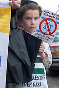 A young Jewish child holding a sign against the State of Israel participate  to the demonstration in walking with his father.