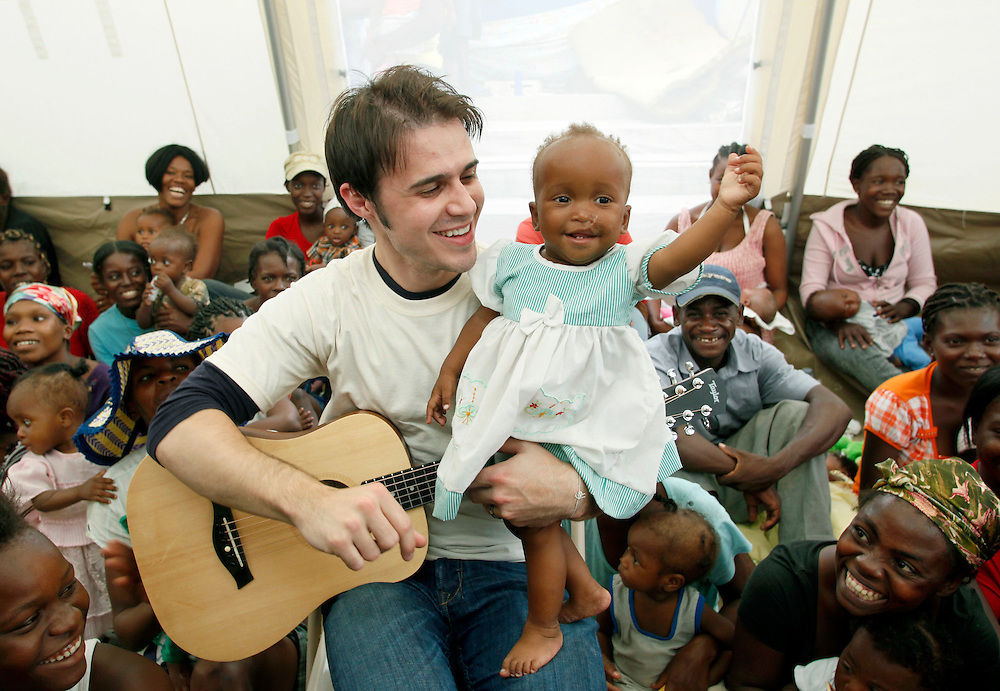 American Idol winner Kris Allen holds a young Haitian girl during a United Nations Foundation visit to recovery and rebuilding programs in Port-au-Prince, Haiti, Friday, Feb. 19, 2010. (Stuart Ramson for United Nations Foundation)