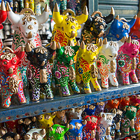 Brightly colored ceramic cow souvenirs on display at the Indian Market in the Miraflores neighborhood of Lima, Peru.