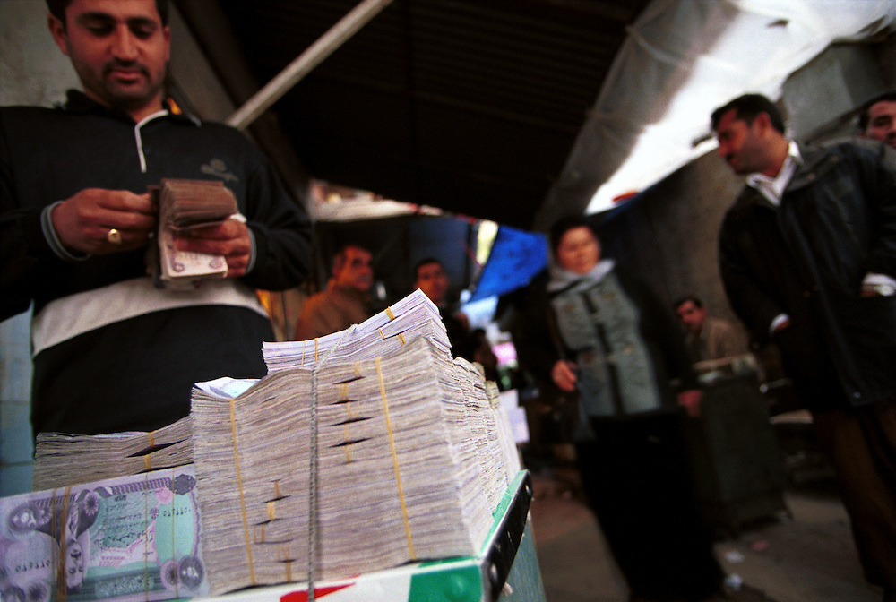 The economy of the Iraqi Kurdistan runs on old Iraqi Dinars printed in Switzerland before the regime of Saddam Hussein. There is virtually no national reserve and no private banks. All the cash of the region is in the hands of the people. The money changers of the Bazaar are Iraqi Kurdistan's money markets. Most of the currencies exchanged are Dollars, Euros, Saddam's new Iraqi Dinars, Turkish lira and Iranian rials, the countries with which most trade and smuggling are conducted...Sulaimaniya, Iraqi Kurdistan. 24/11/2002...Photo © J.B. Russell