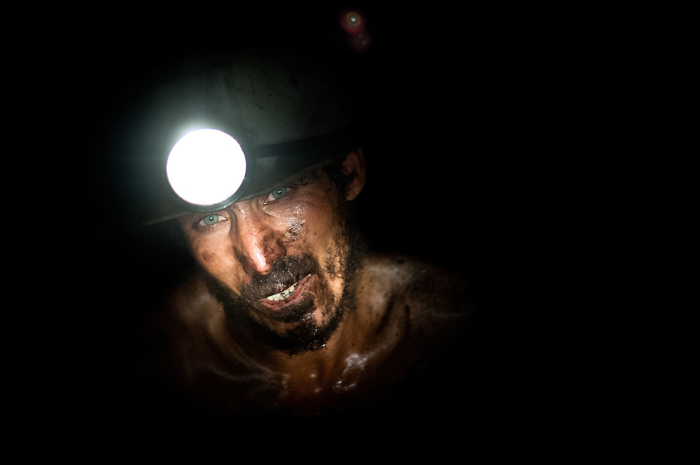 A shirtless miner works in total darkness with primitive equipment in the Karkara coal mine