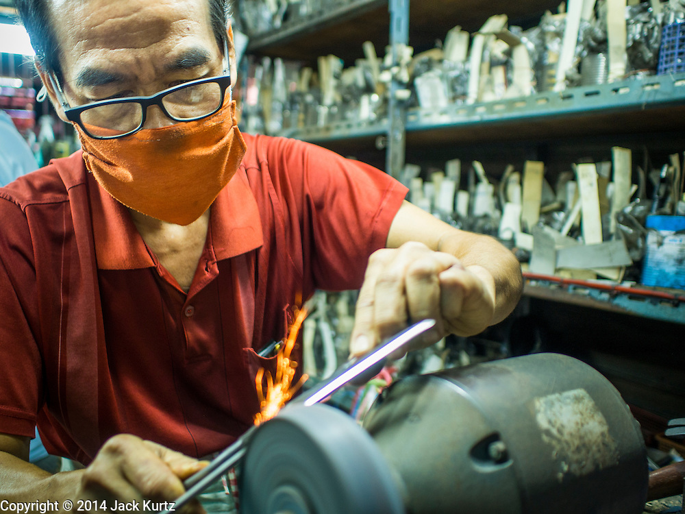 09 DECEMBER 2014 - THONBURI, BANGKOK, THAILAND:  A man who sharpens scissors and knives working in his shop in the market in the Thonburi section of Bangkok.    PHOTO BY JACK KURTZ