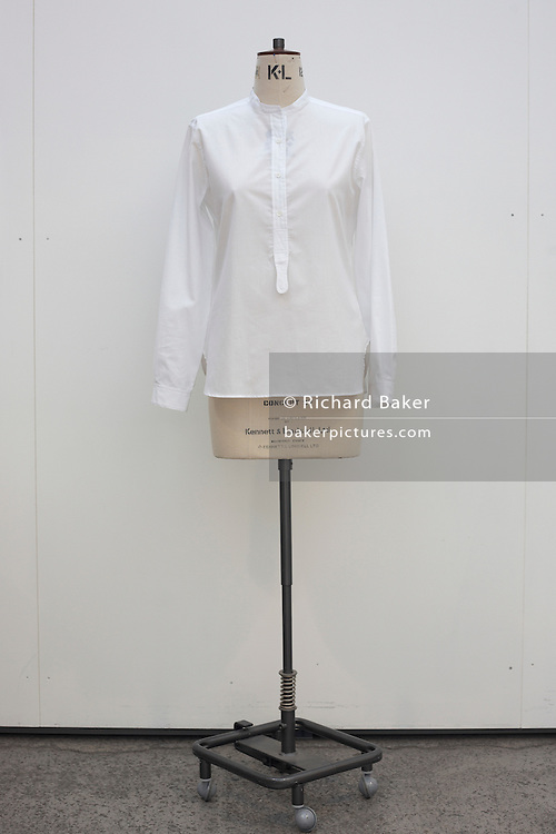 A simple white cotton shirt set on a dressmaker's tailoring dummy in the design studio at couturier Margaret Howell's workshop