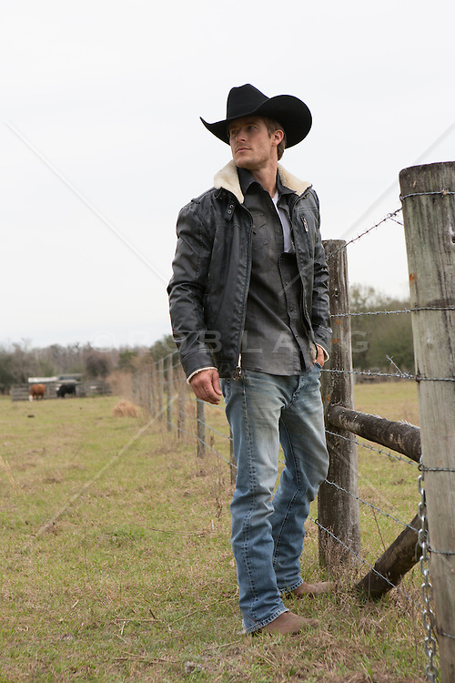 handsome cowboy outdoors by a fence