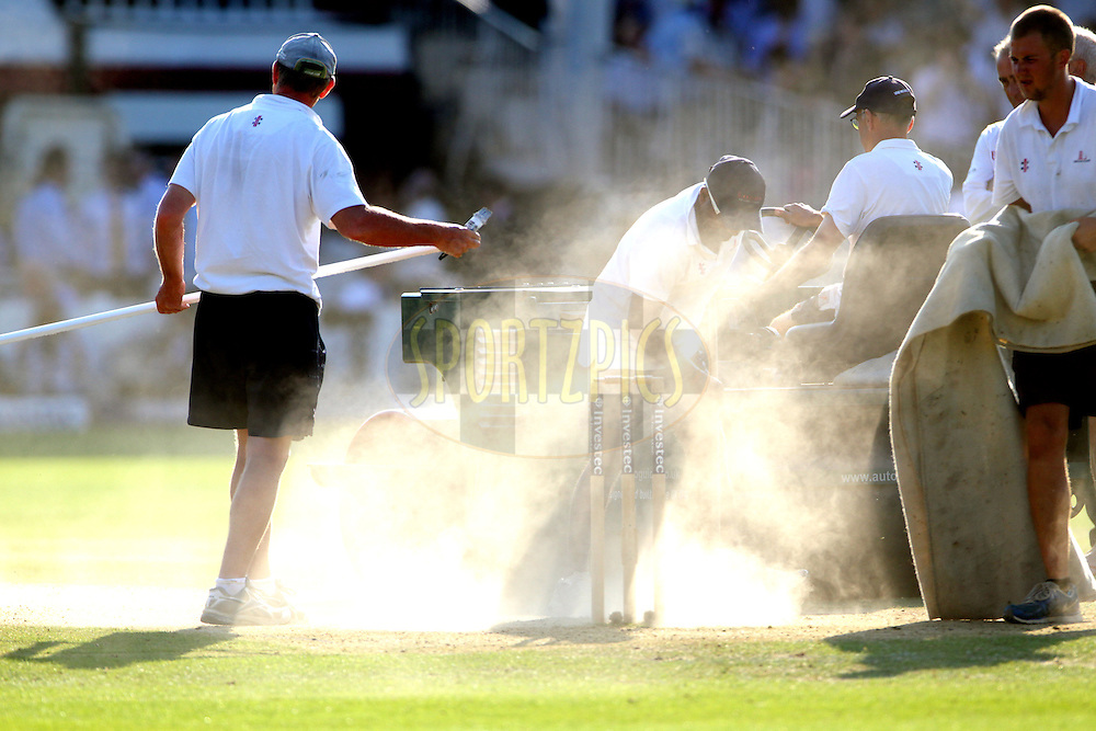 © Andrew Fosker / Seconds Left Images 2012 - Lord's Ground staff sweep the wicket between innings throwing up clouds of dust on a hot day   England v South Africa - 3rd Investec Test Match - Day 4 - Lord's Cricket Ground - 19/08/2012 - London - UK - All rights reserved
