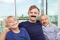 Portrait of father and children with artificial mustache at home