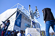 A wide view of the Billy Bremner statue outside Elland Road stadium, as a fan with a half and half scarf takes a photo before to the left, the EFL Sky Bet Championship match between Leeds United and Bolton Wanderers at Elland Road, Leeds, England on 23 February 2019.