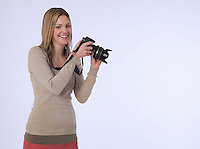 Portrait of young (20-25 years) female photographer holding camera studio shot