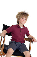 School boy sitting on director's chair over white background