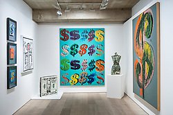 "© Licensed to London News Pictures. 08/06/2015. London, UK.  (L to R) ""Three Dollar Signs"" by Andy Warhol, ""Untitled"" by Keith Haring, ""50 Dollars"" by Jin Wang, ""Dollar Signs"" by Andy Warhol, ""Venus aux dollars"" by Arman and ""Dollar Sign"" by Andy Warhol, at the preview of ""To the Bearer on Demand"", a private collection of 21 works inspired by the US dollar, including Andy Warhol masterpieces, which will be auctioned on 1 and 2 July.  The collection is estimated to realise £50 million. Photo credit : Stephen Chung/LNP"