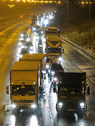 © Licensed to London News Pictures . 23/03/2013 . Rochdale , UK . The M62 motorway closed from Junction 21 Eastbound , at Milnrow , after several lorries became stuck on the freezing roads trying to climb the steep motorway towards Britain's highest motorway peak . The North West Motorway police reported that gritters trying to access the scene to make it safe became stuck too . A car accident also occurred on the Westbound carriageway . Large , stationary traffic queues formed in the closure's wake . Heavy snow and strong winds are creating treacherous driving conditions tonight (22/23rd March 2013) , across the North of England . Photo credit : Joel Goodman/LNP