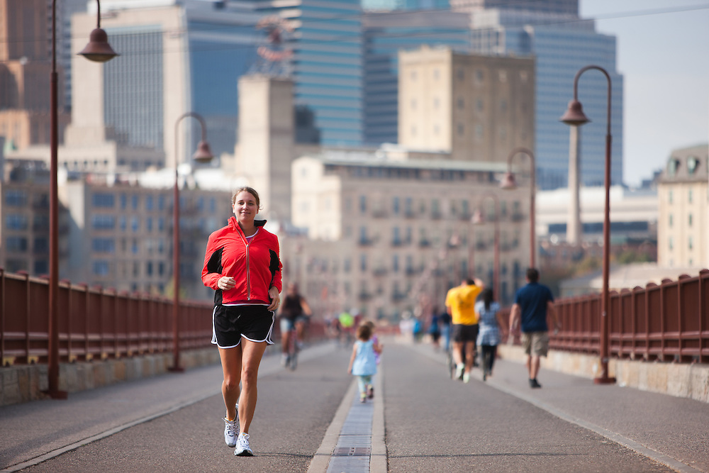 Female jogger crossing Minneapolis' famous Stone Arch Bridge over the Mississippi river. The bridge connects eas and west banks of the Mississippi river and is a popular recreation area.