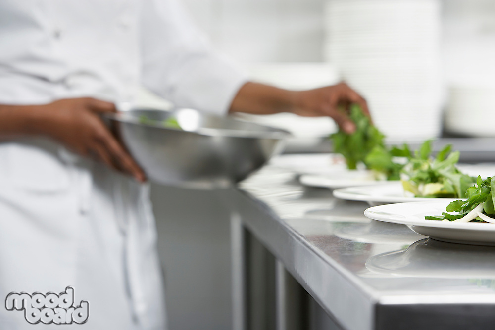 Chef preparing salad in kitchen mid section