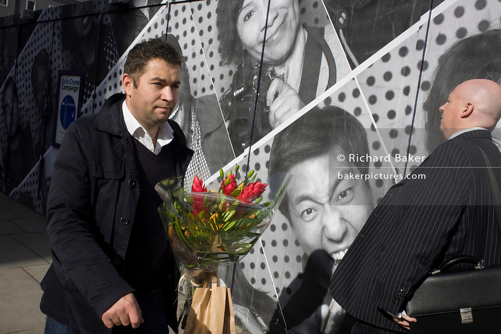 A man carries a bunch of red flowers past a construction hoarding featuring many faces and expressions.