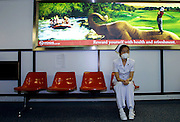 A Thai nurse sits in front of an advertisement for tourism in Thailand as she waits to check passengers arriving from Hong Kong at Bangkok's International Airport. All travelers arriving from high-risk countries in the Asia-Pacific region are being carefully monitored. Thailandís Deputy Prime Minister Somkid Jatusripitak said Sars has cost the tourism industry about 30 billion baht so far. Mr Somkid said the tourism authority attributed the loss to the disease spreading in nearby countries, rather than in Thailand, thereby scaring tourists.