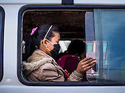 07 MARCH 2017 - KATHMANDU, NEPAL: A passenger on a bus in Kathmandu. People frequently wear masks and breathing filters because of the particulate pollution in the air.      PHOTO BY JACK KURTZ