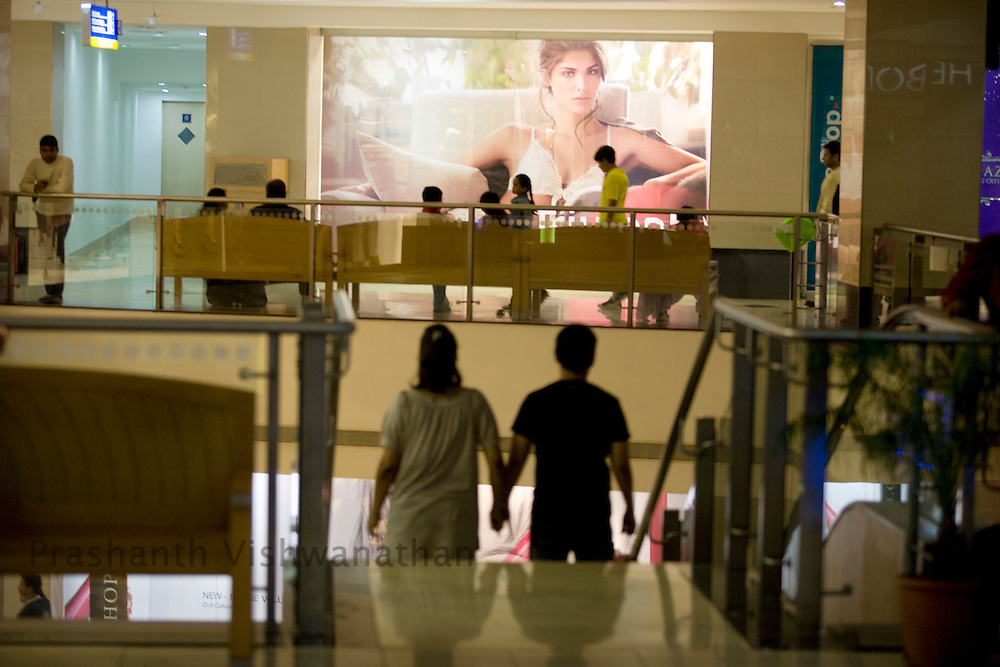 Shoppers walk past advertisements inside the Inorbit Mall Malad, in Mumbai, on Sunday Dec. 28, 2008.  Photographer:Prashanth Vishwanathan