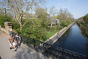 UNITED KINGDOM, London: 09 April 2020 <br /> A couple walk across a bridge over Regent's Canal as the sun shines this afternoon. Temperatures for Easter weekend are set to reach 24C degrees, with a reminder to the public to save lives and help the NHS by staying indoors.