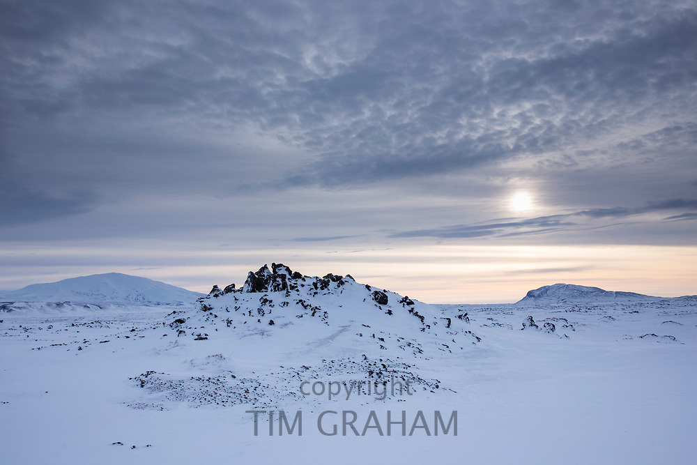 Wintry sun and cloud formation above snow-covered mountains in glacial landscape in South Iceland