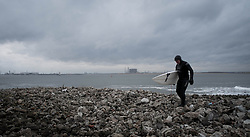 © Licensed to London News Pictures. 18/01/2014<br /> <br /> Teesside, England<br /> <br /> Surfer Mick Jackson walks across rocks after surfing on the North east coast of England.<br /> <br /> Photo credit : Ian Forsyth/LNP