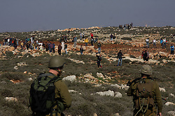 Palestinian protesters throw stones towards Israeli soldiers during clashes near the West Bank village of Qusra, near Nablus city, Israel, January 1, 2013. Photo by Imago / i-Images...UK ONLY